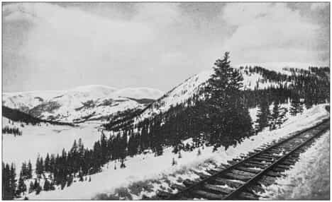 antique photo of snowy American mountains and railroad