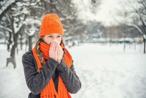 woman blowing her nose in snowy weather